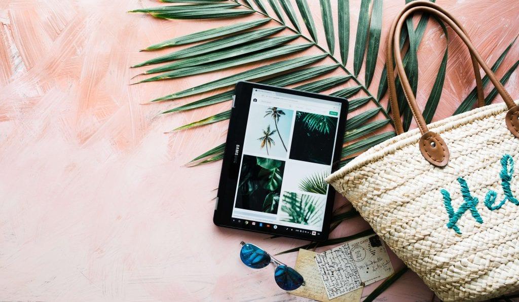 tablet, pink background, summer beach bag, palm leaf, sunglasses Everything Abode.com
