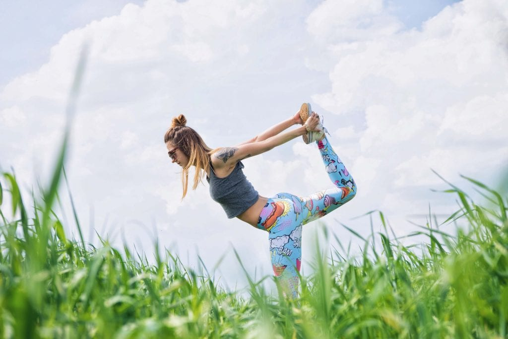 Girl doing Yoga stance in a feild with green grass and a blue sky www.everythingabode.com
