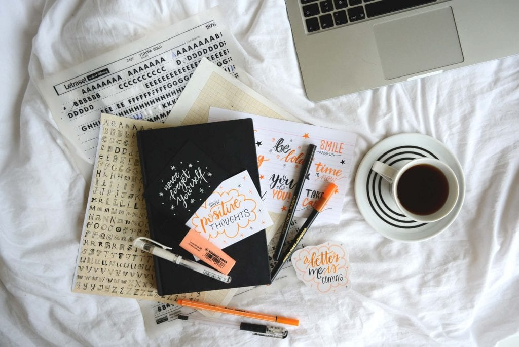 Journal placed on top of a bed. White sheets, wrinkled and cozy, orange pens, white coffee mug with white saucer half full with black coffee. www.everythingabode.com Affiliate Marketing