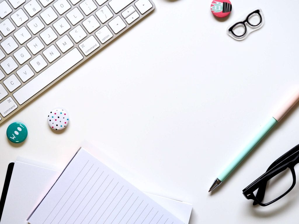 Keyboard, paper, small black eye glasses, blue pen, work station, desk area. www.everythingabode.com Affiliate Strategy
