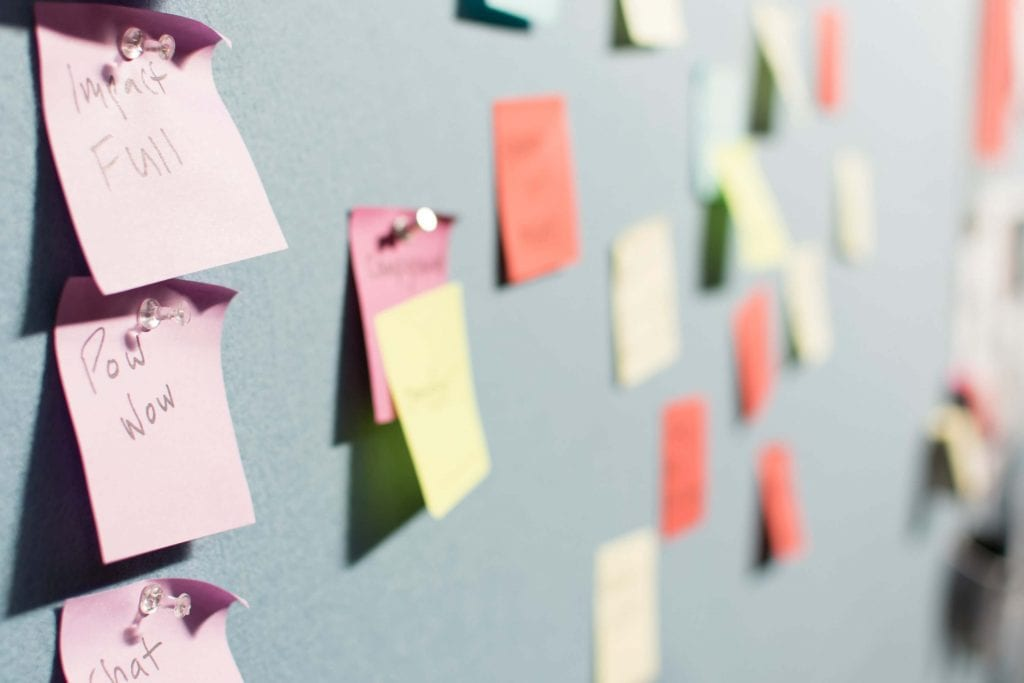 multiple color post it notes, tacked to a blue wall-www.everythingabode.com ways-to-get-more-pinterest-traffic