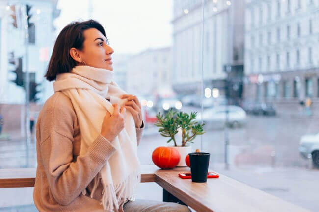 34 Simple Daily Self-Care Ideas For Taking Better Care of Yourself-girl-cozy-cafe-warms-herself-up-with-cup-hot-coffee