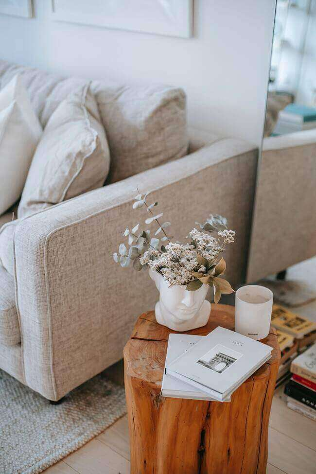 living room items to discard and organize, side table in living room next to grey sofa with a white coffee mug and the side table is a wooden log. Very nice style!