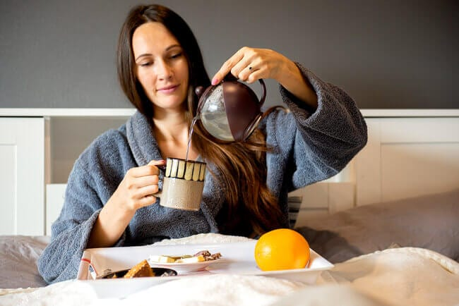 How to prepare for a great night of sleep with food. beautiful-brunette-woman-sitting-bed-holding-tea-cup-
