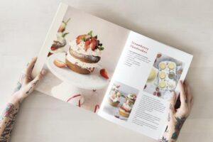 indoor hobby baking, woman holding onto cook book of inspiring pastries to make