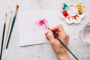 women painting water color flower in pink color on her day off