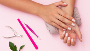 a pair of women's hands showcasing her new gel nails with soft white nail polish as a fun popular indoor hobby for women